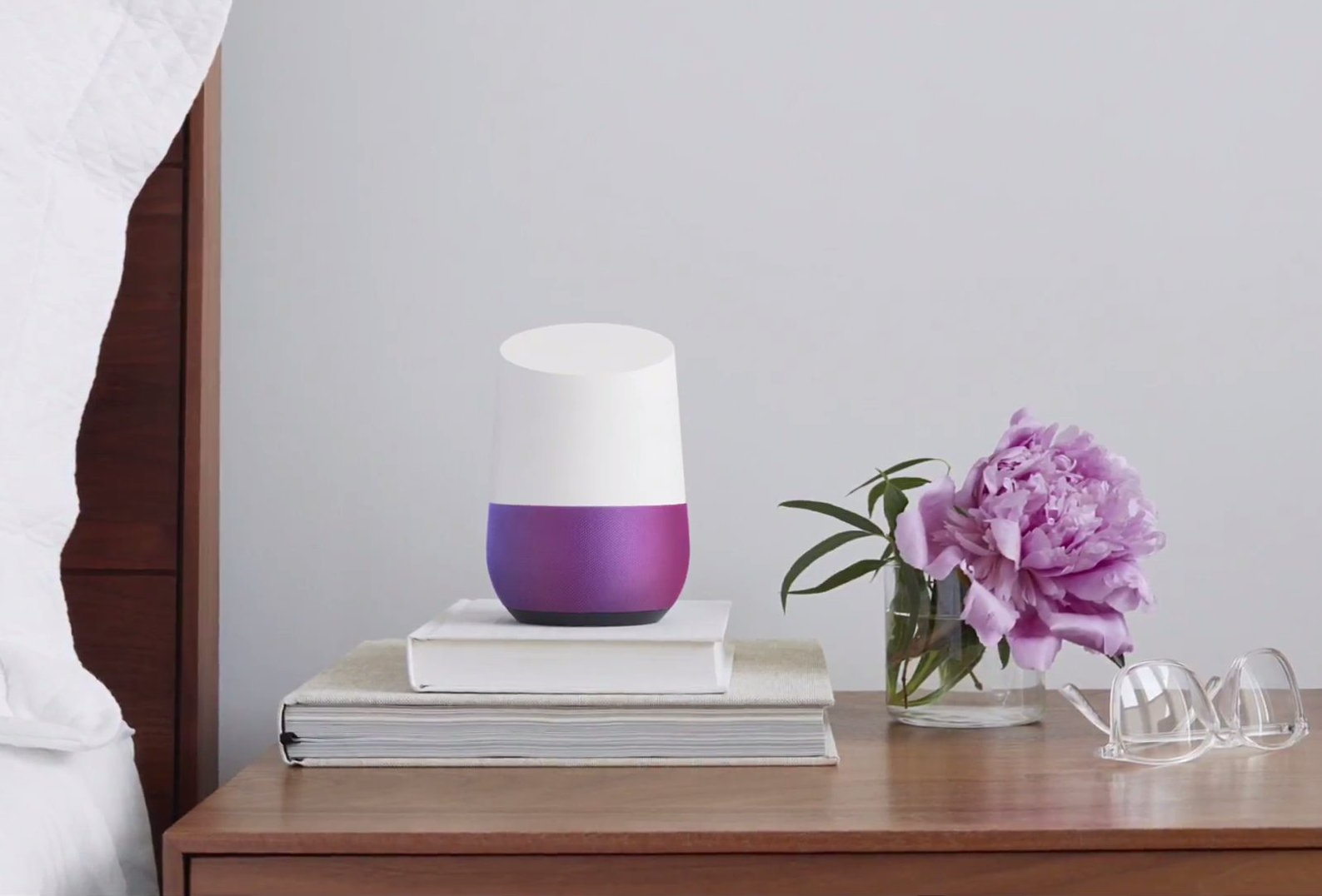 A Google Home device on a bedside table.