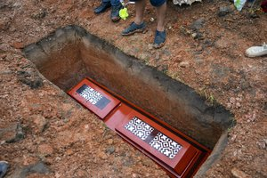Adorned with Indigenous Amazonian Shipibos designs, the coffin containing the remains of Jessica Soria Gonzales, a 50-year-old Shipibo artist who died due to complications related to COVID-19, lies in a freshly dug grave at her graveside ceremony in Pucallpa, in Peru's Ucayali region, Wednesday, Oct. 7, 2020.