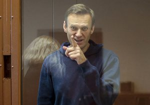 In this photo taken from a footage provided by the Babuskinsky District Court Tuesday, Feb. 16, 2021, Russian opposition leader Alexei Navalny gestures during a hearing on his charges for defamation in the Babuskinsky District Court in Moscow, Russia