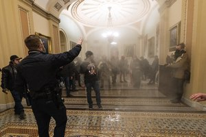 In this Jan. 6, 2021, file photo, smoke fills the walkway outside the Senate Chamber as supporters of President Donald Trump are confronted by U.S. Capitol Police officers inside the Capitol in Washington.