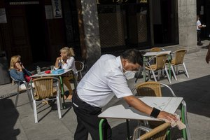 A waiter disinfects a table in downtown Madrid, Spain, Wednesday, Sept. 30, 2020.
