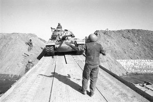 File - Israeli Tanks Cross the Suez Canal during the Yom Kippur War, 1973. The war took place mostly in Sinai and the Golan—occupied by Israel during the 1967 Six-Day War—with some fighting in African Egypt and northern Israel.