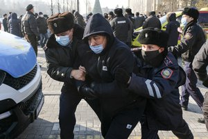 Kazakhstan's police officers detain a protester during an opposition rally in Almaty, Kazakhstan, Sunday, Jan. 10, 2021, as voters in resource-rich Kazakhstan are going to the polls in a parliamentary election lacking any serious opposition.