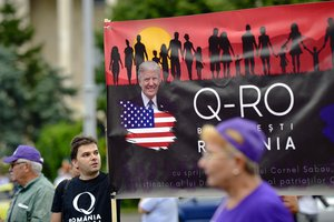 Romanian supporters of QAnon take part in a rally against the government's measures to prevent the spread of COVID-19 infections, like wearing a face mask, in Bucharest, Romania, Monday, Aug. 10, 2020.