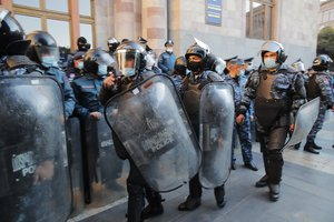 Police guard during a protest against an agreement to halt fighting over the Nagorno-Karabakh region, in front of the government building in Yerevan, Armenia, Wednesday, Nov. 11, 2020