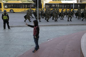 File - In this Nov. 5, 2017 photo, a child reacts to a march past of security personnel in a show of force in Kashgar in western China's Xinjiang region.