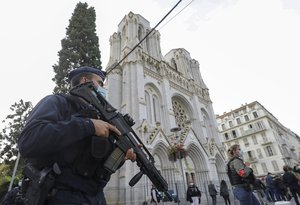 A French police officer stands near Notre Dame church in Nice, southern France, Thursday, Oct. 29, 2020. French President Emmanuel Macron has announced that he will more than double number of soldiers deployed to protect against attacks to 7,000 after three people were killed at a church Thursday.