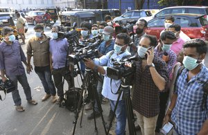 Journalists wearing surgical masks stand outside the government general hospital where a student who had been in Wuhan is kept in isolation in Thrissur, Kerala state, India, Thursday, Jan. 30, 2020.