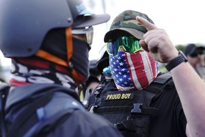 In this Sept. 26, 2020 file photo, a right-wing demonstrator gestures toward a counter protester as members of the Proud Boys and other right-wing demonstrators rally in Portland, Oregon.