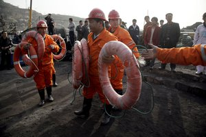 Rescue workers prepare floating aide outside the Wangjialing Coal Mine in Xiangning county in north China's Shanxi province, Sunday, April 4, 2010.
