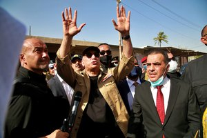 Iraqi Prime Minister Mustafa al-Kadhimi waves to residents of Tarmiyah, where a commander of an Iraqi army brigade was killed last week in an attack blamed on the Islamic State group, in Tarmiyah, 35 kilometers (20 miles) north of Baghdad, Iraq, Monday, July 20, 2020.