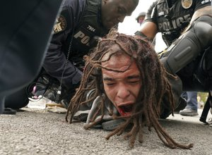Police detain a man after a group marched in protest over a lack of charges against Louisville police in Breonna Taylor's death, Wednesday, Sept. 23, 2020, in Louisville, Kentucky.